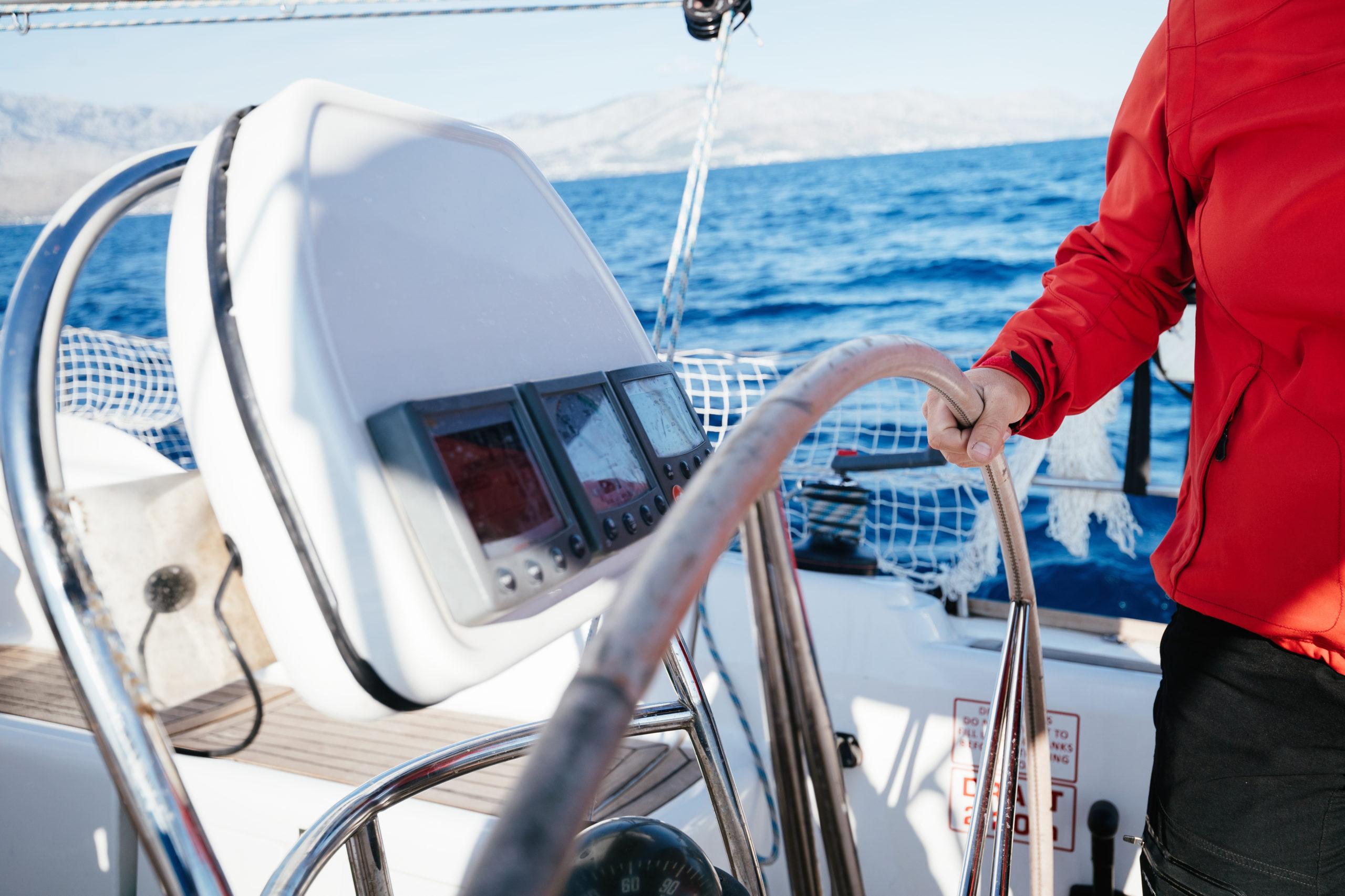 Yacht captain hand on yacht steering wheel
